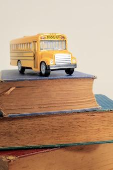 黄色のスクールバスグッズモデルと古い本。ビンテージ背景。