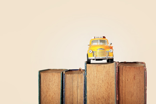 노란색 스쿨 버스 장난감 모델과 오래 된 책입니다. 빈티지 배경입니다.