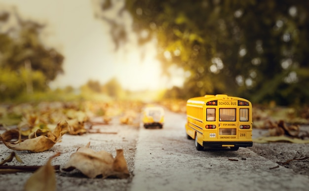 Yellow school bus toy model on country road.