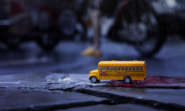 Yellow school bus (toy model) during hard rain fall in city,low angle view and shallow depth of field composition.