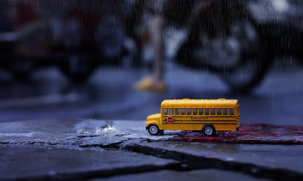 激しい雨の中に黄色のスクールバス(おもちゃのモデル)が街に落ちる、低角度のビュー、フィールド構成の浅い深さ。