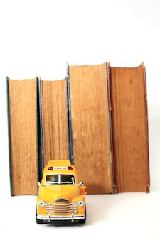 Yellow school bus toy model and old books.vintage background.