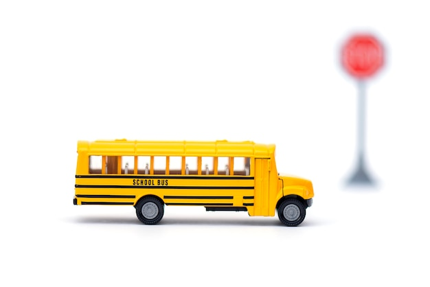 Yellow school buss, toy with blurred stop sign on white background