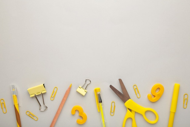 Yellow school supplies on grey background. back to school concept. top view.