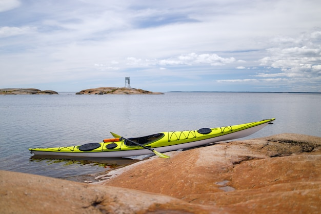 Yellow sea kayak on the granite shore in focus. background is blurred.
