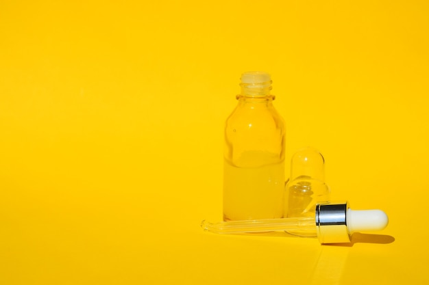 드롭퍼가있는 투명한 병에 노란색 혈청 액체 오일