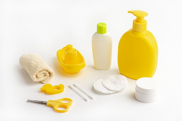 Yellow shampoo bottle, towel, cotton pads and toy boat on white.