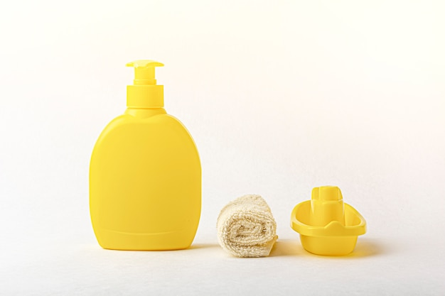 Yellow shampoo bottle, towel and toy boat on white.