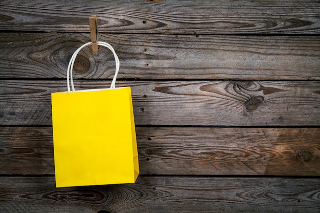 Желтая хозяйственная сумка на деревянном фоне, продажа, покупка