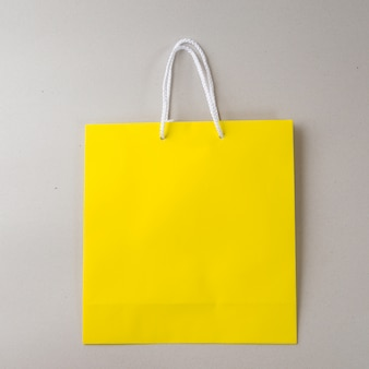 Yellow shopping bag one white background and copy space for plain text or product