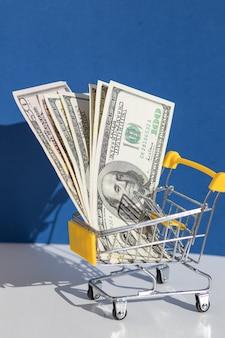 黄色のショッピングカートとドル、オンラインショッピングのコンセプト。オンラインショッピングの販売と食料品のカートの創造的なプロモーションの組成物。