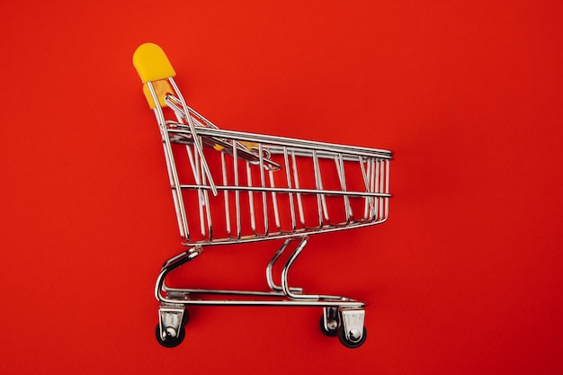 Yellow shopping cart isolated on red