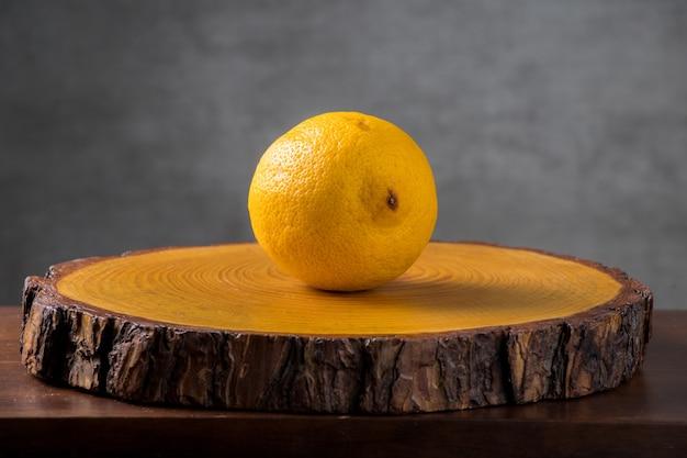 Желтый сицилийский лимон. на деревенском срезе дерева с серым фоном. копировать пространство.