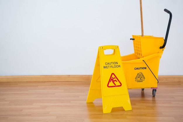 Yellow sigh boad with mop bucket on floor against wall