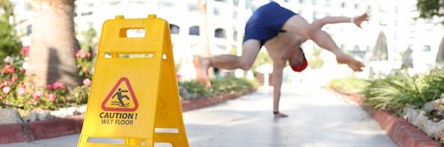 Желтый знак осторожно, мокрый пол, стоя возле падающего человека крупным планом
