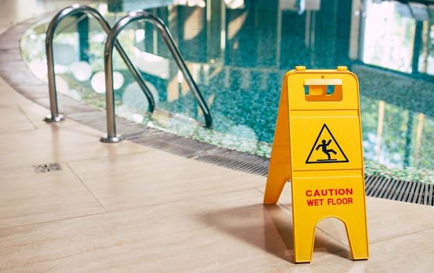 Желтый знак мокрого пола возле бассейна.