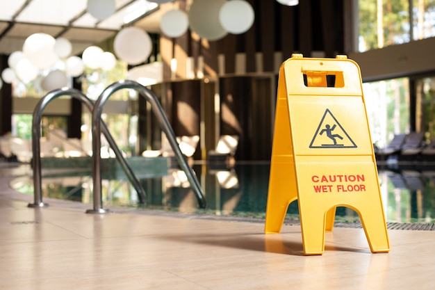 Yellow sign of wet floor plate is near the swimming pool.