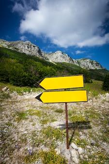 높은 산 경로에 서있는 노란색 푯 말
