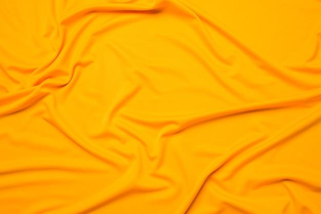 Yellow silk folded fabric background