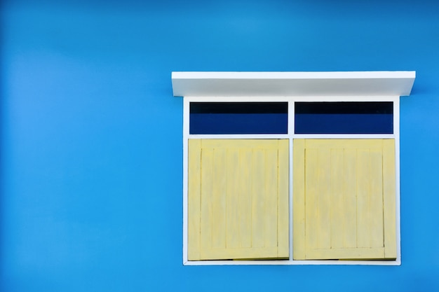 Yellow simple vintage window with white awning isolated on blue cement wall background