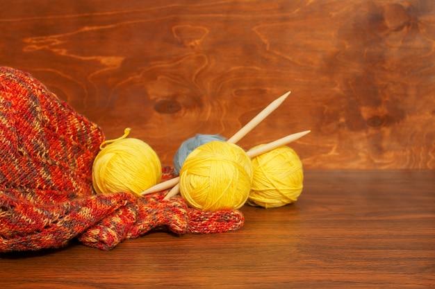Желтые мотки, спицы и вязаный шарф на деревянной поверхности