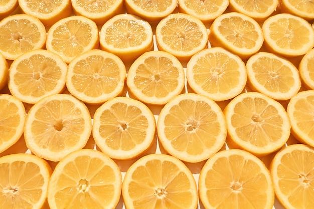 黄色のスライスしたレモンがテーブルの上に置かれますかわいいスライス新鮮なジューシーなテクスチャー