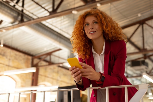 Yellow smartphone. curly beautiful woman wearing smart watch holding yellow smartphone