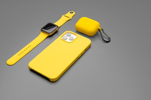 Желтый смартфон, умные часы и наушники на сером фоне крупным планом