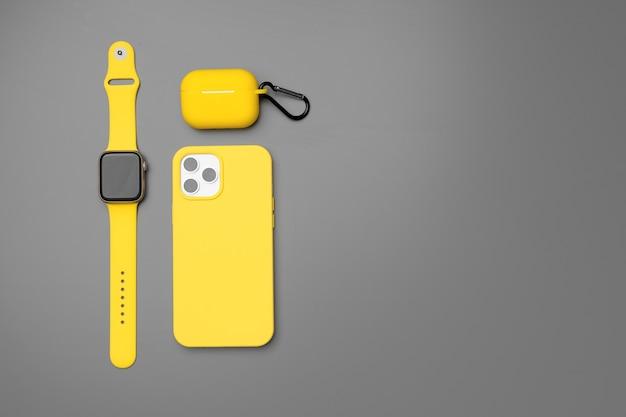 Смарт-часы и наушники желтого смартфона на сером фоне