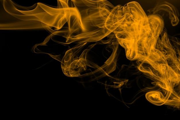 Yellow smoke abstract on black background, yellow ink on dark
