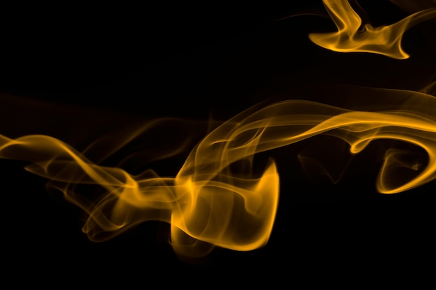 Yellow smoke abstract on black background, yellow ink on dark