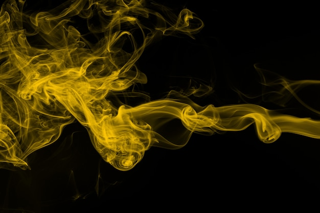 Yellow smoke on black background, abstract movement