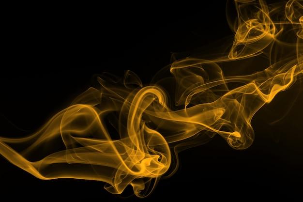 Yellow smoke on black background, yellow ink on dark