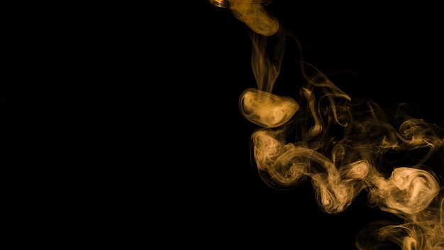 Yellow smoke curl on black background with copy space for writing the text