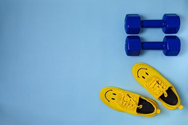 Желтые кроссовки и синие гантели на голубом фоне с копией пространства