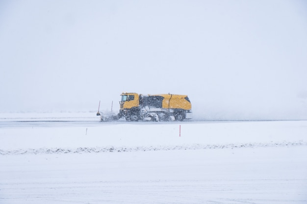 Yellow snow ploughs plowing snow covered road in blizzard