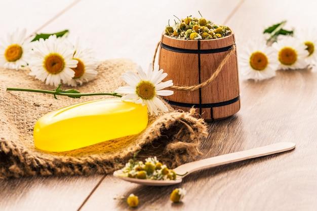 荒布に黄色い石鹸、新鮮なカモミールの花束と背景に小さな木製の樽。自然化粧品とスパ製品
