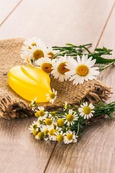 木の板に新鮮なカモミールの花束と荒布に黄色い石鹸。自然化粧品とスパ製品