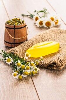 荒布に黄色い石鹸と新鮮なカモミール、小さな木製の樽とゆるい葉のカモミールティー