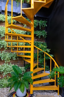 Yellow spiral staircase with plants on brick wall