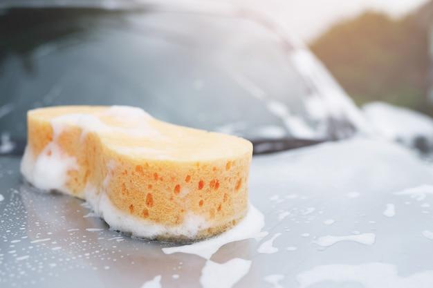 세차를 위해 차 위에 노란색 스폰지와 비누. 모터 후드를 청소하고 있습니다. 깔끔한 컨셉의 세차장. 메시지를 작성할 공간을 남겨두십시오.