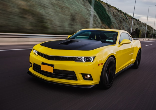 Yellow sport car with black autotuning on the road.