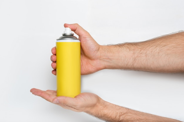 Yellow spray can for spraying in a male hands