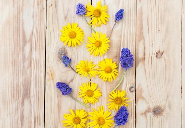 黄色い春の花が木製の背景に配置されています。上面図。