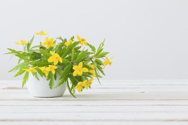 白い背景の上の花瓶に黄色の春の花