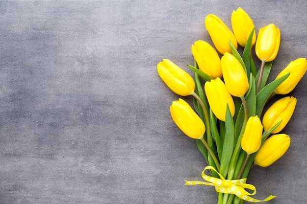黄色い春の花、灰色の背景にチューリップ。