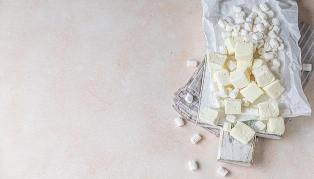 나무 절단 보드에 노란색 사각형 모양의 마시멜로와 흰색 바닐라 마시멜로 프리미엄 사진