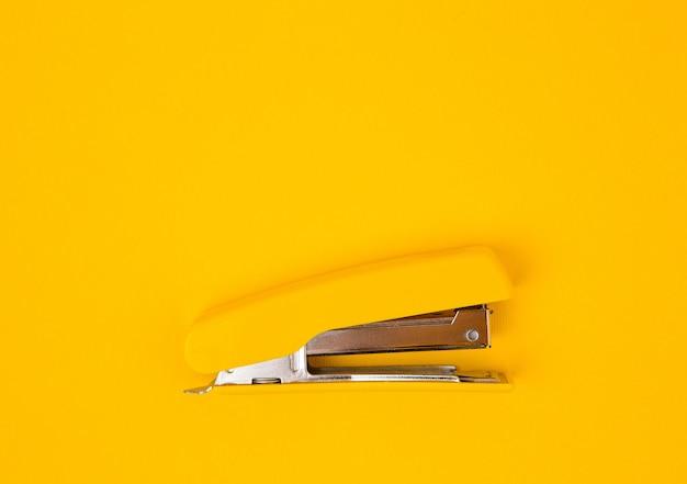 Желтый степлер на желтом