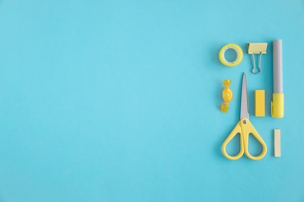 黄色の文房具とキャンデー、青い背景