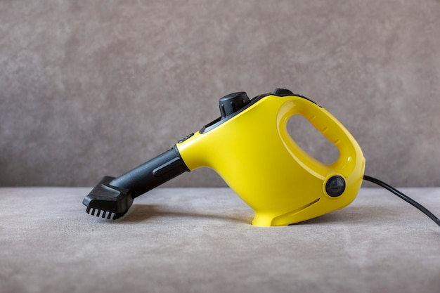 Yellow steam cleaner with brush stands on brown sofa